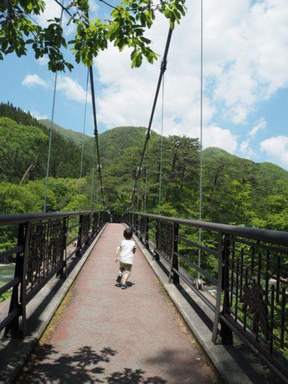滝の奥にある吊り橋を渡っている写真です